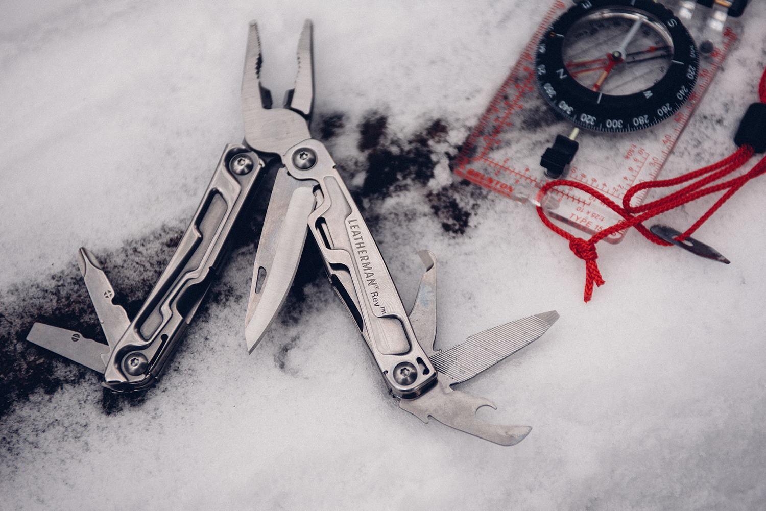 Multi-Tool in snow next to compass.