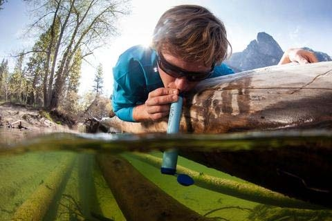 Man drinking through water filtration straw from polluted water.