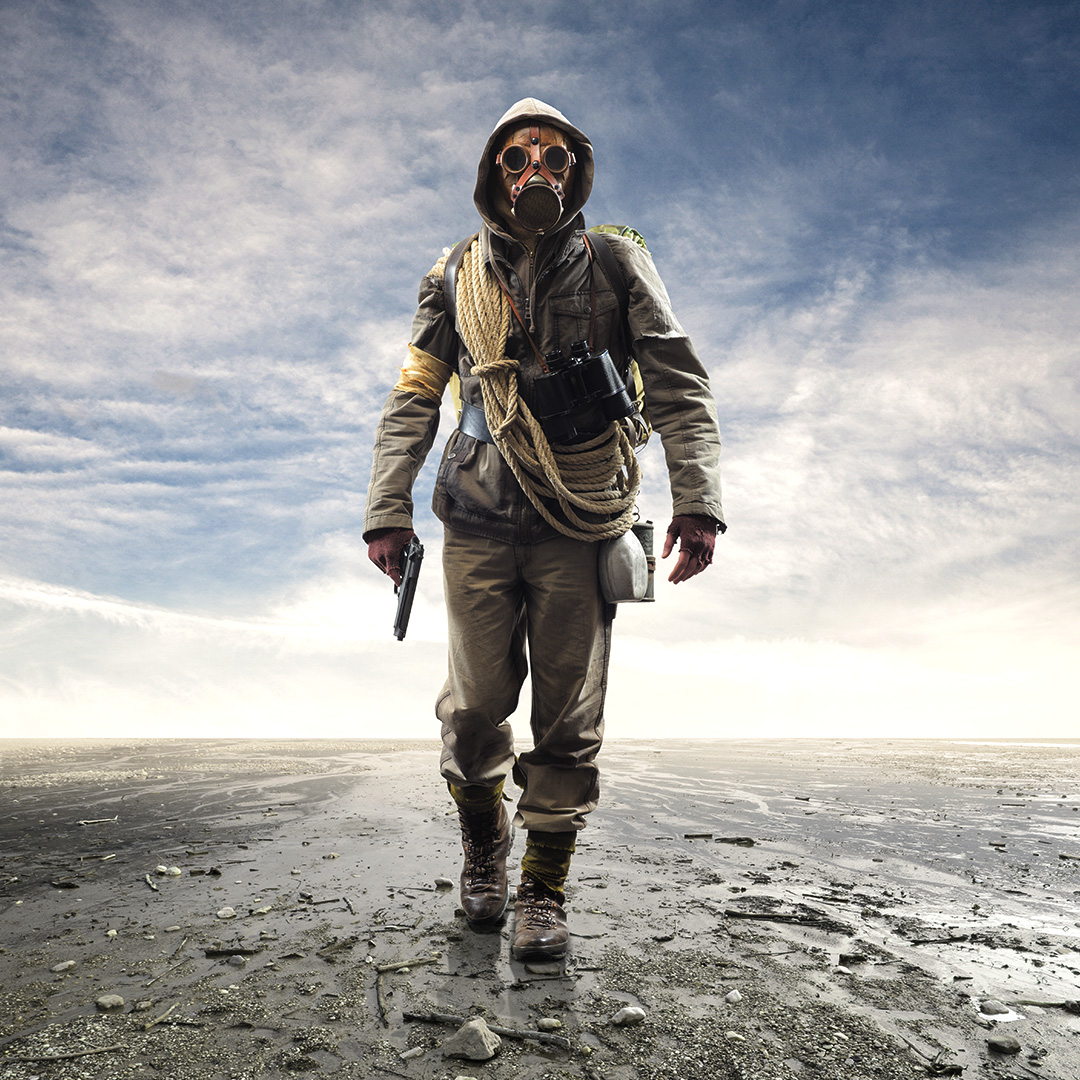 Person in various survival gear in a post-apocalyse wasteland.