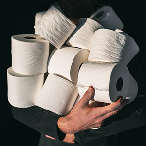 Person holding large hoard of toilet paper.