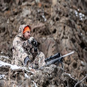 man in hunting clothes scouting deer