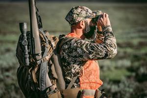 hunter using binoculars for observation