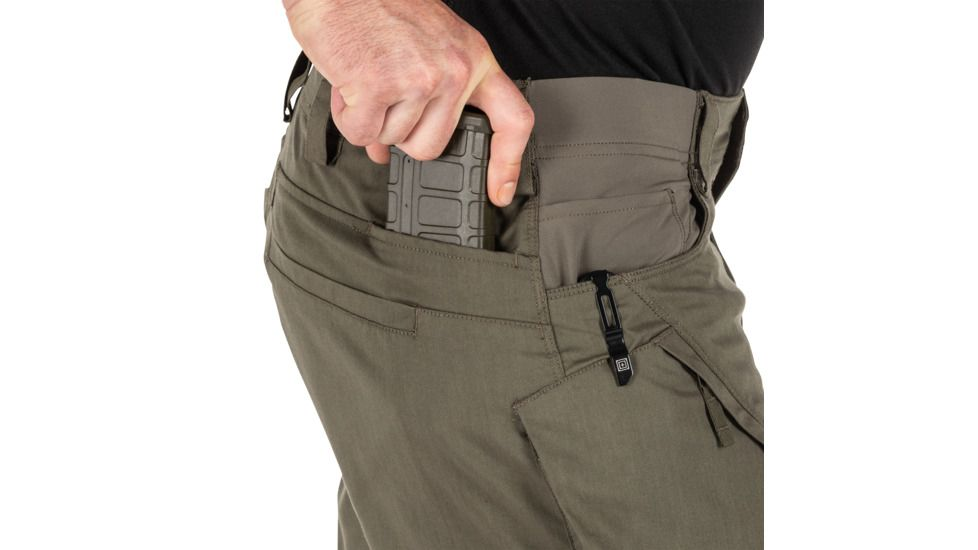 man putting magazine in pocket of tac pants
