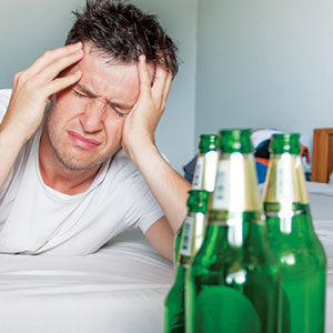 Man with empty bottles of beer holding his head.