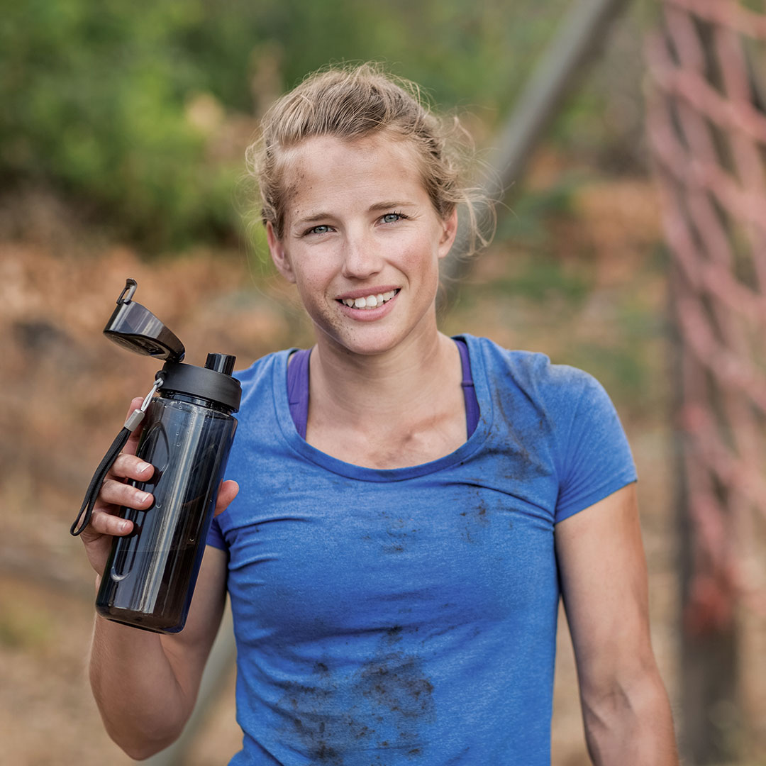 Woman holding water bottle outside.