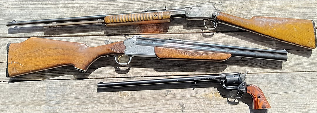 Three guns on a wood background.