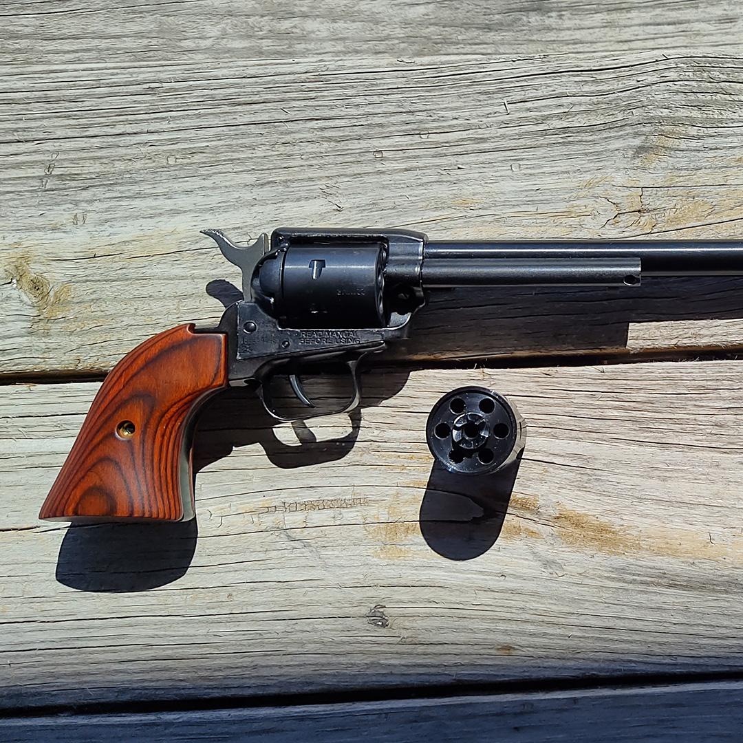 Revolver handgun with extra cylinder on wood background.