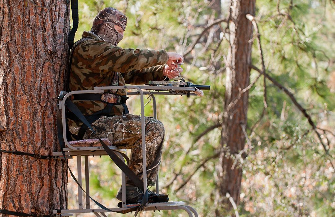 deer hunter wearing camo sitting in tree stand