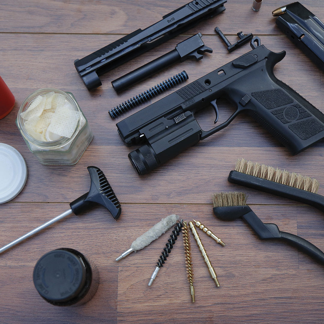 A pistol taken apart with cleaning supplies around it.