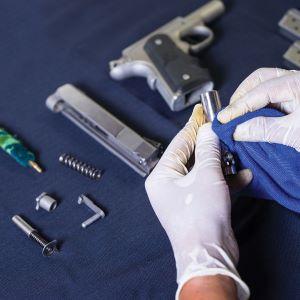 man cleaning gun with kit supplies