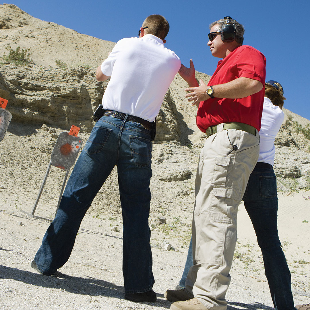 Student at the outdoor shooting range getting advice from a firearms instructor.